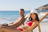 Young couple on their deck chairs smiling at camera