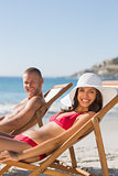 Couple on their deck chairs smiling at camera