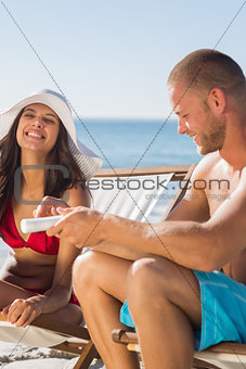 Attractive man applying sun cream on his girlfriend