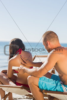 Handsome man massaging his girlfriend with sun cream