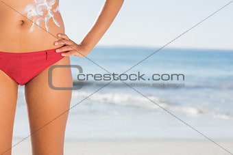 Toned woman body with sun cream pattern
