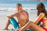 Smiling woman putting sun cream on her boyfriends back