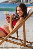 Cheerful pretty woman drinking cocktail while relaxing on her deck chair
