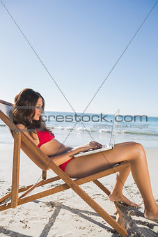 Woman using her laptop while relaxing on her deck chair