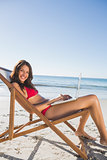Pretty woman using her laptop while relaxing on her deck chair