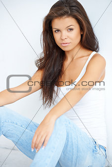 Cute teenage girl is sitting on the floor