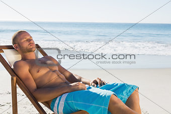 Handsome man having a nap while sunbathing on his deck chair