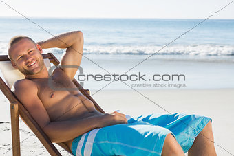 Smiling handsome man sunbathing on his deck chair