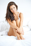 Beautiful woman sitting on white bed