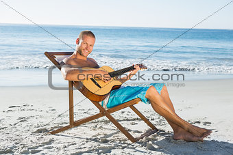 Cheerful handsome man playing guitar