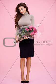 Beautiful brunette with bunch of pink roses