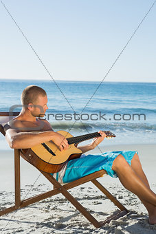 Focused handsome man strumming guitar