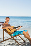 Cheerful handsome man strumming guitar