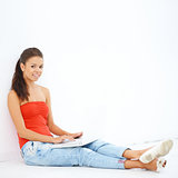 Young smiling girl sitting on the floor with laptop