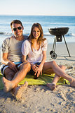 Cheerful couple posing while having barbecue