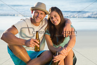 Smiling couple embracing while having a drink together