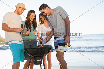 Smiling young friends having barbecue together