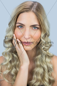 Thoughtful gorgeous blond model posing touching her face