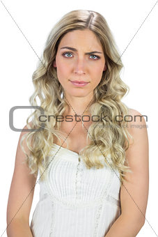 Blond model in white dress rising her eyebrow
