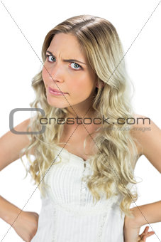 Angry blond model in white dress frowning at camera