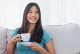Young asian woman drinking cup of tea
