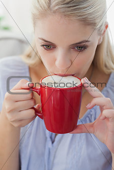 Blonde woman holding a mug and sipping from it