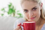 Blonde woman holding a red mug and smiling at camera