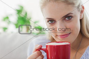 Blonde woman holding a red mug and smiling at camera