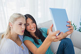 Two happy friends taking photo with tablet pc