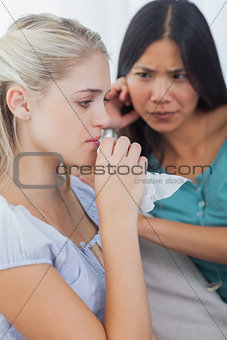 Blonde crying and talking as her concerned friend is listening