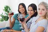 Cheerful friends having red wine together looking at camera