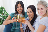 Cheerful friends enjoying white wine together smiling at camera