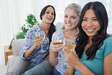 Happy friends having white wine together looking at camera