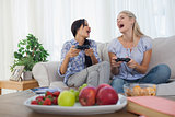 Laughing friends playing video games and having fun