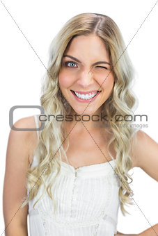 Smiling blue eyed model winking at camera