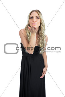 Attractive blonde with black cocktail dress sending a kiss to camera