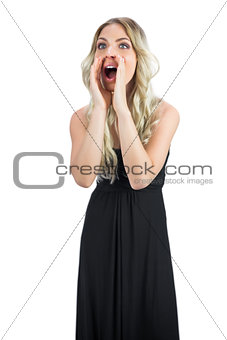 Attractive blonde wearing black dress shouting