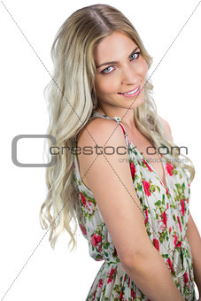 Smiling attractive blonde wearing flowered dress posing