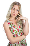 Frowning pretty blonde wearing flowered dress posing
