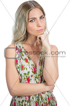 Thoughtful pretty blonde wearing flowered dress posing