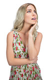 Pensive pretty blonde wearing flowered dress posing