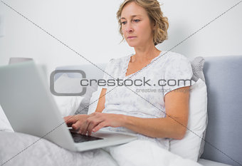 Blonde woman sitting in bed using laptop