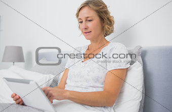 Blonde smiling woman sitting in bed using tablet pc