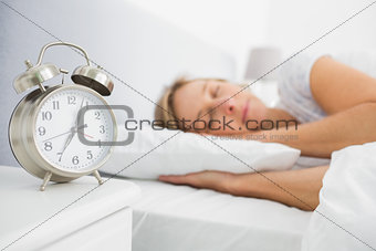 Blonde woman asleep in bed while her alarm shows the early time