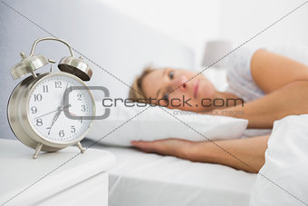 Blonde woman lying in bed while her alarm shows the early time
