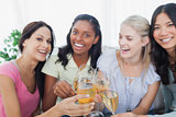 Friends toasting with white wine and smiling at camera