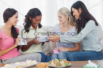 Friends offering gifts to dark woman during party