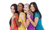 Diverse young women laughing at camera and embracing