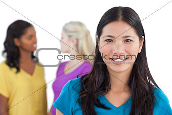 Smiling asian woman looking at camera with two women behind her