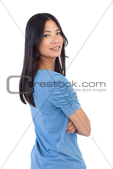 Smiling asian woman with arms crossed looking over her shoulder